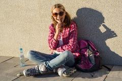Una muchacha fresca sonriente de los jóvenes, calzada en pcteres de ruedas, se sienta en el si Fotos de archivo libres de regalías