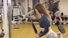 Una muchacha fuerte delgada entrena a un tríceps en una cruce en el gimnasio metrajes