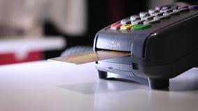Una muchacha hace una compra con un banco o la tarjeta de crédito usando un microprocesador electrónico en la tarjeta Inserte una almacen de video