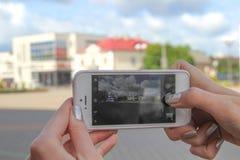 Una muchacha hace una foto en la ciudad en el teléfono imagen de archivo