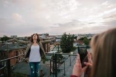 Una muchacha hace la foto de su amigo en el tejado Imagenes de archivo