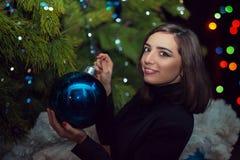 Una muchacha hermosa adorna un árbol de navidad en el ` s Eve del Año Nuevo Fotografía de archivo