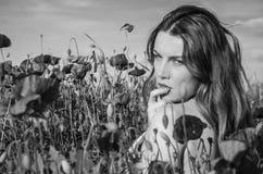 Una muchacha hermosa alegre joven camina en un prado de la amapola entre amapolas florecientes del rojo en un día de verano brill Fotos de archivo