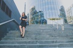 Una muchacha hermosa camina abajo de las escaleras que habla en el teléfono Imagenes de archivo