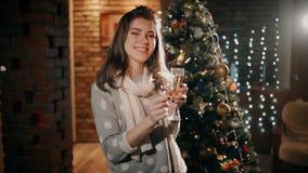 Una muchacha hermosa con una bengala en su mano está bebiendo el champán y está riendo en la Navidad metrajes