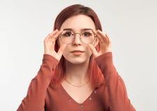 Una muchacha hermosa con el pelo multicolor lleva a cabo dos manos detr?s del borde de sus vidrios imagen de archivo