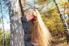 Una muchacha hermosa con el pelo rizado largo, mirando a escondidas hacia fuera de detrás Imagen de archivo