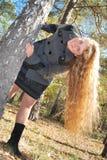 Una muchacha hermosa con el pelo rizado largo, mirando a escondidas hacia fuera de detrás Foto de archivo