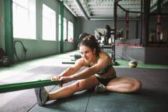 Una muchacha hermosa con una sonrisa estira sus músculos, amasa, calienta antes de entrenar en una junta con una goma Fotos de archivo
