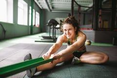 Una muchacha hermosa con una sonrisa estira sus músculos, amasa, calienta antes de entrenar en una junta con una goma Imagen de archivo libre de regalías