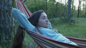 Una muchacha hermosa con sus mentiras flojas del pelo en una hamaca Una mujer joven en una chaqueta gris está descansando sobre u metrajes