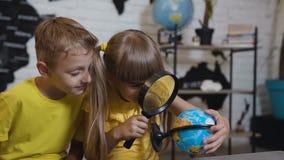 Una muchacha hermosa con un muchacho a través de la lupa mira el globo en la sala de clase En una lección de la geografía almacen de metraje de vídeo