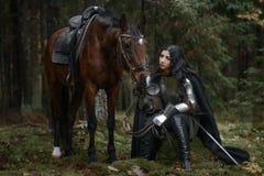 Una muchacha hermosa del guerrero con un chainmail que lleva de la espada y armadura con un caballo en un bosque misterioso imagenes de archivo