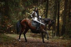 Una muchacha hermosa del guerrero con un chainmail y una armadura que llevan de la espada que montan un caballo en un bosque mist imagenes de archivo