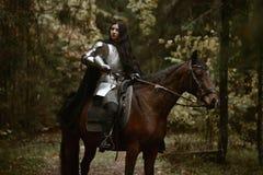 Una muchacha hermosa del guerrero con un chainmail y una armadura que llevan de la espada que montan un caballo en un bosque mist fotos de archivo