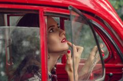 Una muchacha hermosa del perno-para arriba en una camisa de tela escocesa corrige maquillaje en el salón de un coche retro rojo v imagenes de archivo