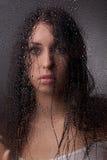 Una muchacha hermosa detrás del vidrio. Imágenes de archivo libres de regalías