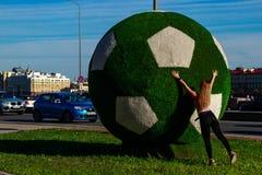 Una muchacha hermosa empuja una bola verde grande para el fútbol La bola adorna St Petersburg para el mundial en 2018 fotografía de archivo