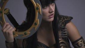 Una muchacha hermosa en armadura del oro se está preparando para lanzar un disco de la batalla metrajes