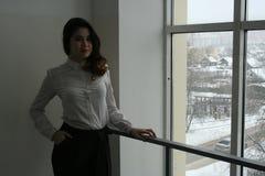 Una muchacha hermosa en una blusa blanca está esperando al lado de la ventana fotografía de archivo