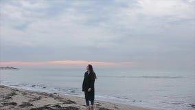 Una muchacha hermosa en una capa larga de la primavera que camina en la playa en la salida del sol almacen de metraje de vídeo