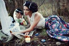 Una muchacha hermosa en el bosque quema letras Imagenes de archivo