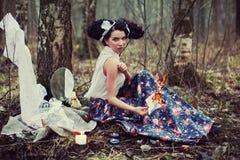 Una muchacha hermosa en el bosque quema letras Fotografía de archivo
