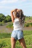 Una muchacha hermosa en la frontera de un lago Imagen de archivo libre de regalías