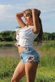 Una muchacha hermosa en la frontera de un lago Imágenes de archivo libres de regalías