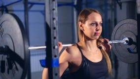 Una muchacha hermosa en ropa de deportes ajustada negra para el hacer de ejercicios con un barbell Front View almacen de video