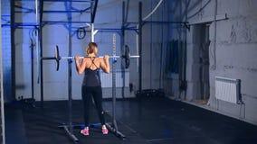Una muchacha hermosa en ropa de deportes ajustada negra para el hacer de ejercicios con un barbell Visión posterior almacen de video