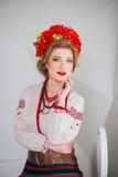 Una muchacha hermosa en traje ucraniano nacional Capturado en estudio Bordado y chaqueta Guirnalda Anillo de flores Labios rojos Imagen de archivo libre de regalías