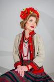 Una muchacha hermosa en traje ucraniano nacional Capturado en estudio Bordado y chaqueta Guirnalda Anillo de flores Labios rojos Imagen de archivo