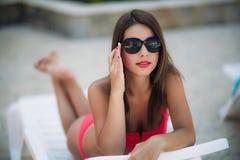 Una muchacha hermosa en un bañador rosado que toma el sol por la piscina tiempo soleado Verano imagenes de archivo