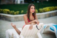Una muchacha hermosa en un bañador rosado que toma el sol por la piscina tiempo soleado Verano imagen de archivo