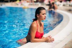 Una muchacha hermosa en un bañador rosado que toma el sol por la piscina tiempo soleado Verano foto de archivo libre de regalías