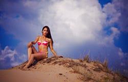 Una muchacha hermosa en un bikiní vierte la arena Imagen de archivo libre de regalías