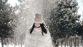 Una muchacha hermosa en un parque del invierno juega feliz con nieve, ella lanza para arriba un brazado de nieve sobre su cabeza, almacen de metraje de vídeo