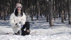 Una muchacha hermosa en un pino que el parque disfruta del tiempo nevoso del invierno, ella lanza juguetónamente para arriba un b almacen de metraje de vídeo