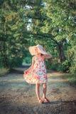 Una muchacha hermosa en un sombrero rosado en los rayos de la puesta del sol en una tarde del verano en la naturaleza imágenes de archivo libres de regalías