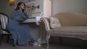 Una muchacha hermosa en un traje azul se sienta al lado de un piano viejo metrajes