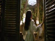 Una muchacha hermosa en un vestido blanco del vintage abre las puertas en la terraza metrajes
