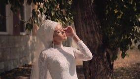 Una muchacha hermosa en un vestido blanco que toma el sol en los rayos de la luz del sol hermosa Aturdir el marco elegante almacen de metraje de vídeo