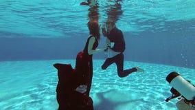 Una muchacha hermosa en un vestido rojo y un individuo en una nadada del traje debajo del agua en la piscina y presentar para un  almacen de video
