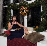 Una muchacha hermosa en un vestido se sienta cerca de la ventana del ` s del Año Nuevo y bebe una bebida caliente Imagen de archivo