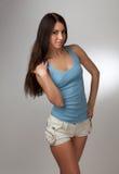 Una muchacha hermosa en una camiseta azul con un CCB gris Imagenes de archivo