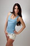 Una muchacha hermosa en una camiseta azul con un CCB gris Fotos de archivo