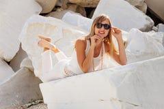 Una muchacha hermosa en vidrios oscuros miente en una piedra blanca imagen de archivo