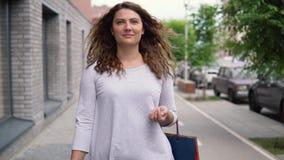 Una muchacha hermosa está caminando abajo de la calle de la ciudad después de hacer compras 4K almacen de metraje de vídeo