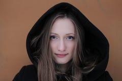Una muchacha hermosa joven con los ojos y la capilla expresivos Foto de archivo